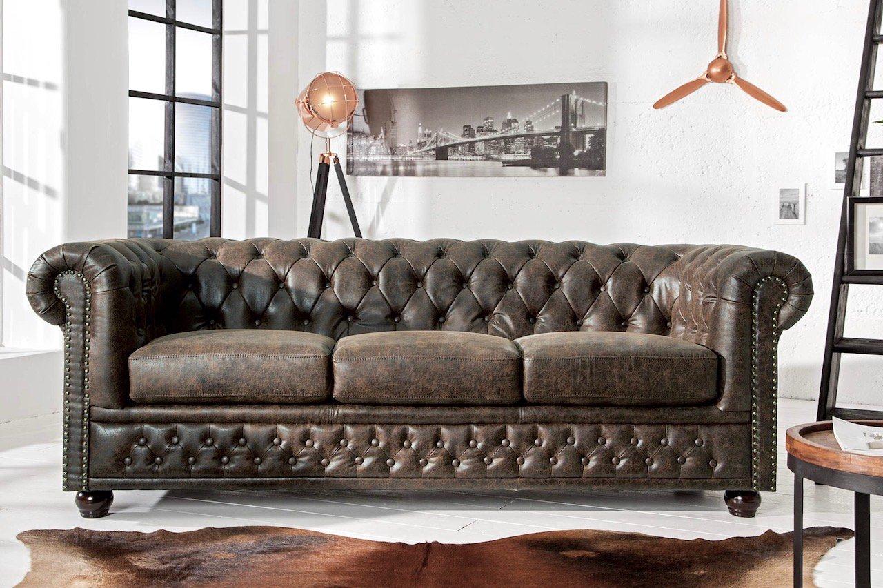 Troj-sedačka Chesterfield je čalúnená bycast kožou v módnom Vintage prevedení. Zažite klasický dizajn a vynikajúce remeselné spracovanie v absolútnej dokonalosti! Impozantná pohovka s typickými rysmi štýlu Chesterfield, ako sú zakrivené opierky, bohato zdobené gombíky, prešívané operadlo a ozdobné ručne vsadené cvočky.